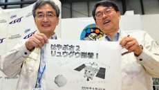 "Professor Takashi Kubota, right, and Associate Professor Makoto Yoshikawa, both of JAXA, the Japanese space agency, pose for photo,  after asteroid explorer Hayabusa2 has arrived at the asteroid of Ryugu, in Sagamihara, near Tokyo, Wednesday, June 27, 2018. The Japanese space explorer arrived at an asteroid Wednesday after a three and half a year journey and now begins its real work of trying to blow a crater to collect samples to eventually bring back to Earth. The words in center, read ""Hayabusa2 has arrived Ryugu"". (Daisuke Suzuki/Kyodo News via AP)"
