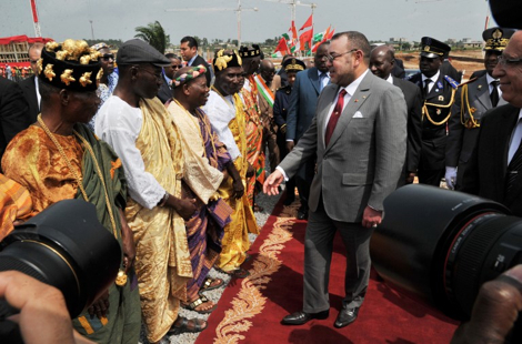 Morocco's King Mohammed VI (C), flanked by Ivory Coast's Prime Minister Daniel Kablan Duncan (4th R), shakes hands with traditional chiefs on a social housing construction site contracted by Moroccan companies, on February 26, 2014 in Anyama, near Abidjan. Ivory Coast's government has signed deals with Moroccan companies to build over 26000 social housing residences in Abidjan and its suburbs.  AFP PHOTO / ISSOUF SANOGO